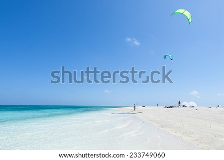 Kitesurfers preparing on coral sand cay beach with clear tropical water, Kume Island, Okinawa, Japan - stock photo
