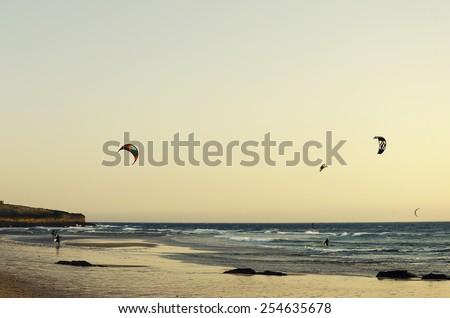 Kitesurfing on the beach at sunset. Summer sports - stock photo