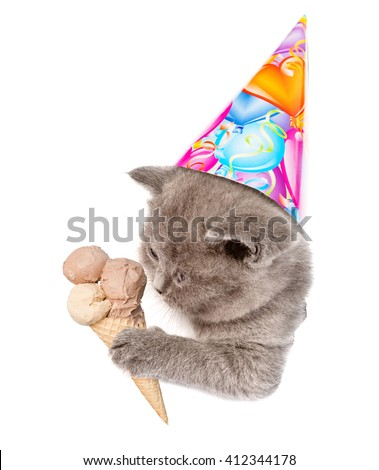 Kitten in birthday hat with ice cream peeking out of a hole in a paper. isolated on white background - stock photo