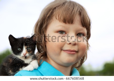 kitten on the arm of the boy outdoors, child huge his love pet
