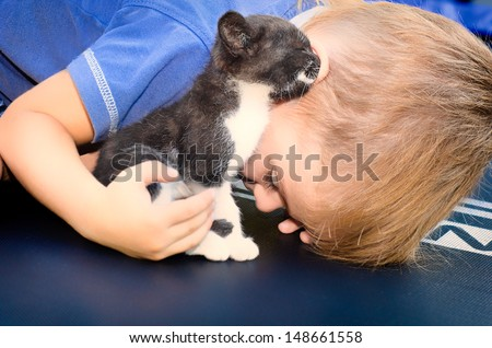 Kitty shares the secret with a little boy - stock photo