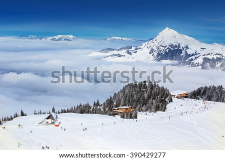KITZBUEHEL, AUSTRIA - February 18, 2016 - Skier skiing and enjoying the view to Alpine mountains in Austria from Kitzbuehel ski resort with 54 cable cars and 170 km prepared skiing slopes.
