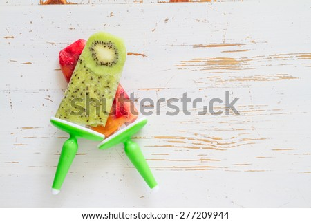 Kiwi and berry fruit ice pops, white wood background, top view - stock photo