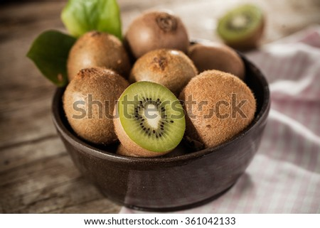Kiwi fruit in a bowl on rustical wooden table