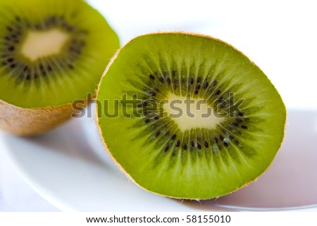 Kiwi fruit sliced in half on a white plate.
