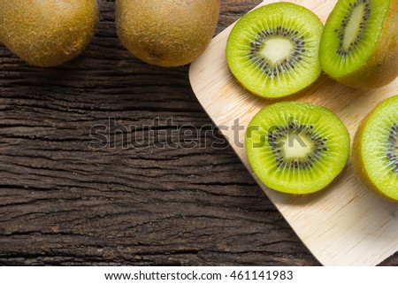 Kiwi fruit slices on wooden background. Copy space