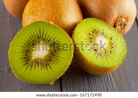 Kiwi in two halves with other kiwis on the back - stock photo