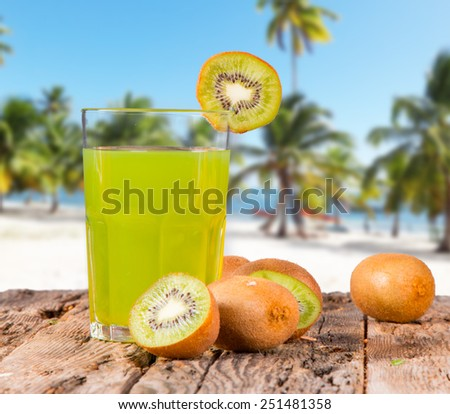 Kiwi juice on wooden with tropical beach  - stock photo