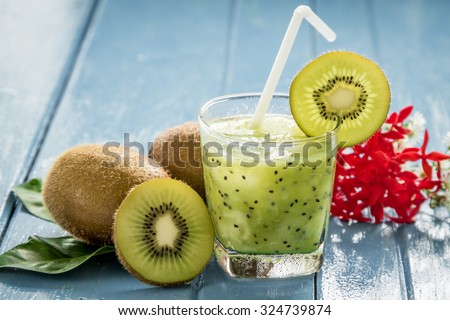 kiwi juice with fresh fruits on blue wooden table - stock photo