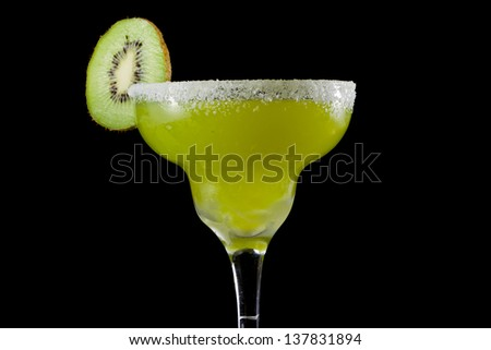 kiwi mellon margarita served with a salt rim isolated on a black background