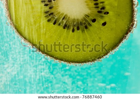 Kiwifruit cocktail - in soda water - against an electric blue background