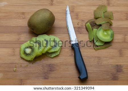 Kiwifruit on a wooden chopping board with a knife.  There is one uncut kiwifruit and some round peeled and cut slices. - stock photo