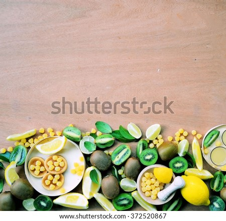 kiwis and lemons, the lemon detox water and sugar on wooden background with space for text