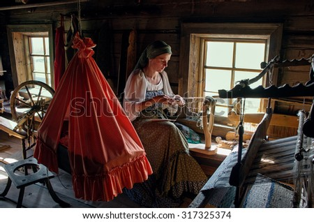 KIZHI, RUSSIA -  AUG 07, 2015: Women in traditional russian costume  weaves  in Historico-architectural museum Kizhi on Kizhi island, Karelia, Russia.  - stock photo