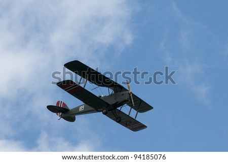 KJELLER AIRPORT, NORWAY - MAY 29: De Havilland DH82 Tiger Moth seen at an airshow on May 29,2011 at Kjeller Airport, Norway. The air plane is seen from below with blue sky as background.