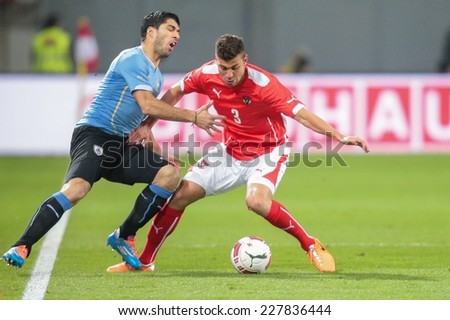 KLAGENFURT, AUSTRIA - MARCH 05, 2014: Aleksandar Dragovic (#3 Austria) and Luis Suarez (#9 Uruguay) fight for the ball in a friendly soccer game between Austria and Uruguay. - stock photo