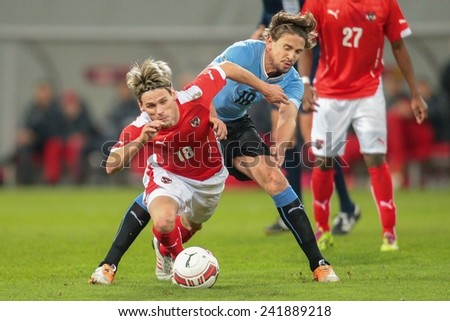 KLAGENFURT, AUSTRIA - MARCH 05, 2014: Christoph Leitgeb (#18 Austria) and Gaston Ramirez (#18 Uruguay) fight for the ball in a friendly soccer game between Austria and Uruguay. - stock photo