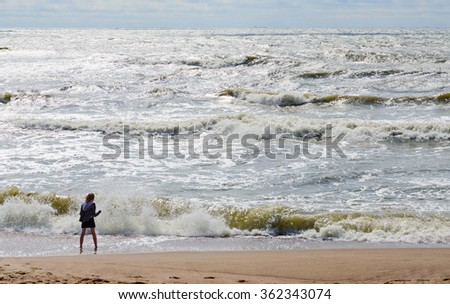 KLAIPEDA, LITHUANIA - JULY 11, 2015: A girl stands on the shore of the restless Baltic Sea