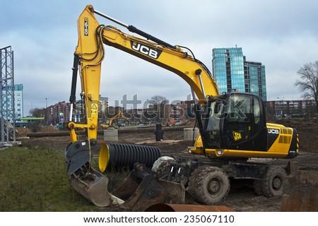KLAIPEDA,LITHUANIA-NOV 24:excavator on road repair on November 24,2014 in Klaipeda,Lithuania. - stock photo