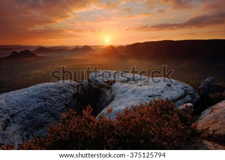 Kleiner Winterberg, beautiful morning view over sandstone cliff into deep misty valley in Saxony Switzerland, foggy background, the fog is orange due to sunrise, star sun on sky, Germany - stock photo