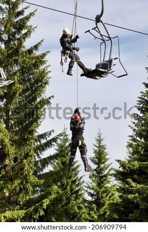 """Klinovec, Czech Republic, June 7, 2012: Training of rescue teams on a chairlift at ski resort Klinovec. Practicing emergency rescue passengers. Klinovec is the highest mountain in the """"Krusne hory"""" - stock photo"""