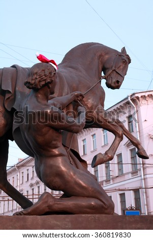 Klodt statue with horse and young man in St. Petersburg, Russia. Christmas hat on mans head - stock photo