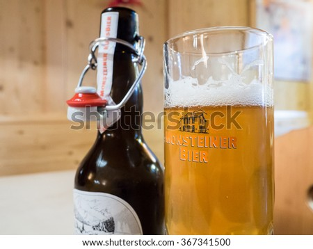 KLOSTERS, SWITZERLAND - JANUARY 15 , 2015 : A view of glass and bottle of monsteiner beer in Klosters. - stock photo