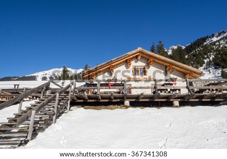 KLOSTERS, SWITZERLAND - JANUARY 15 , 2015 : Cottage Garfiun nearby the Klosters trail in snow covered landscape. - stock photo
