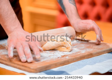 Kneading the dough. Side view of handsome male baker kneading the dough on the wooden cutting board with rolling pin - stock photo