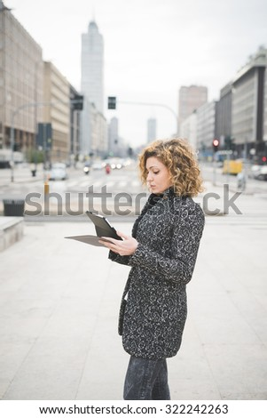 Knee figure of a young beautiful caucasian contemporary businesswoman walking through the streets of the city using a tablet looking the screen - technology, network, business, finance concepts