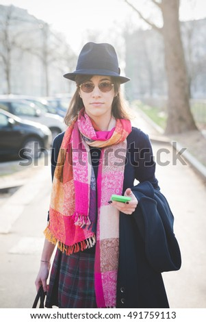 knee figure of a young pretty brown hair woman walking in town using smartphone, looking in camera, pensive - technology, social network, communication concept