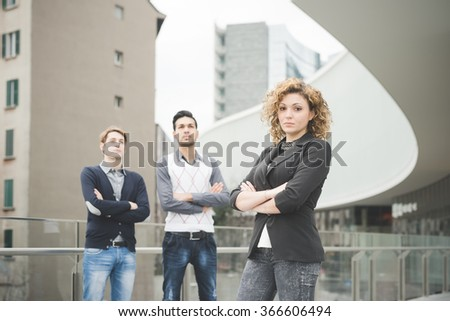 Knee figure of multiracial business people working posing outdoor in the city, with one's arms folded, looking in camera, serious - seriousness, business, determination concept - focus on the woman - stock photo