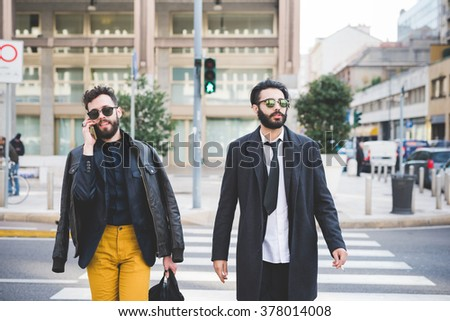 Knee figure of two young handsome businessmen walking outdoor in the city, one talking smartphone holding a bag, the other smoking a cigarette overlooking - business, technology, work concept