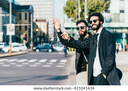 Knee figure of two young handsome caucasian bearded brown hair businessmen outdoor in the city, asking for a taxi - business, technology, communication concept - stock photo