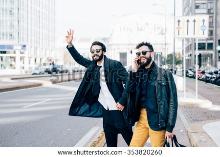Knee figure of two young handsome caucasian bearded brown hair businessmen outdoor in the city, one asking for a taxi, the other talking smartphone - business, technology, communication concept - stock photo