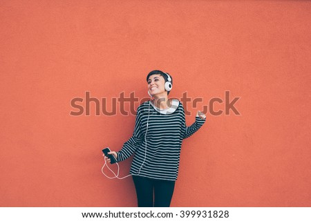Knee figure of young beautiful caucasian woman listening music with headphones and smart phone hand hold, dancing, eyes closed smiling, leaning on a orange wall - music, happiness, technology concept - stock photo