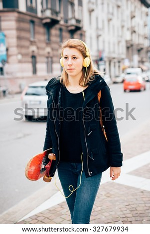 Knee figure of young beautiful hipster sporty blonde woman walking in the street with skate and headphones, listening music, overlooking - music, sportive concept - wearing black jacket and blue jeans