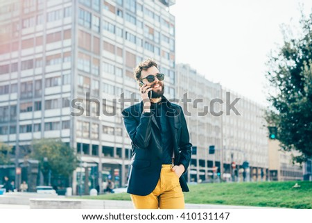 Knee figure of young handsome caucasian bearded man walking outdoor in the city, talking smart phone - communication, business, happiness concept