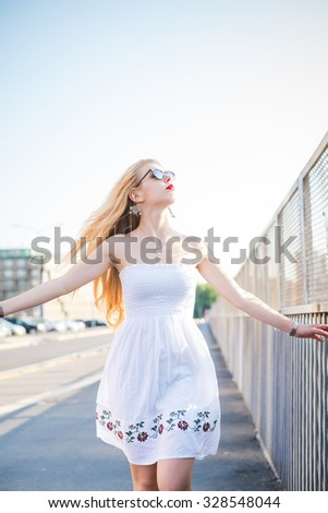 Knee figure of young handsome caucasian long blonde straight hair woman walking in the city, overlooking left, feeling free with arms wide open - wearing white dress - freedom, carefreeness concept - stock photo