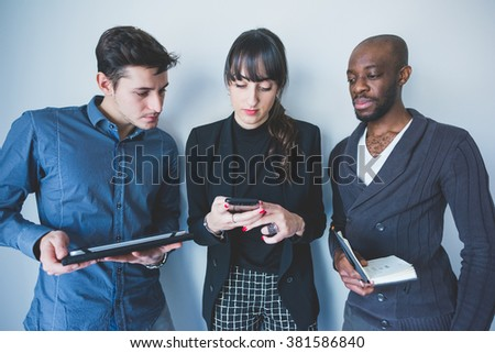 Knee figure of young handsome multiethnic businesspeople working together using technological devices like smartphone and tablet - business, working, teamwork concept - stock photo