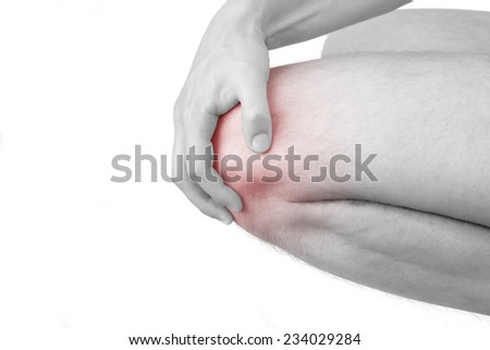 Knee injury. Man holding his knee with highlighted pain are isolated on white background. Health and medicine. - stock photo