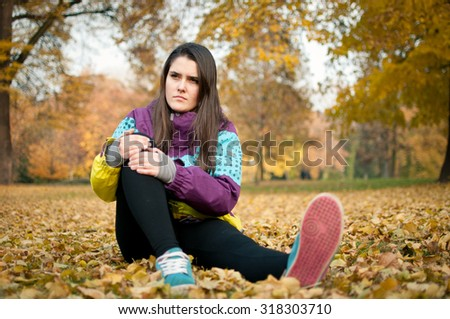 Knee injury - woman sitting in pain - stock photo