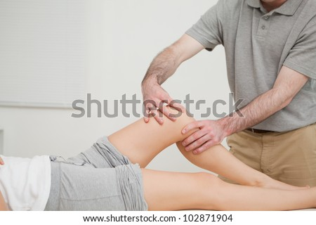 Knee of a woman being massaged by a physiotherapist in a room - stock photo