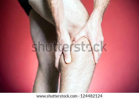 Knee Pain, man holding leg, making massage with hands. Physical injury and recovery or rehabilitation concept. - stock photo