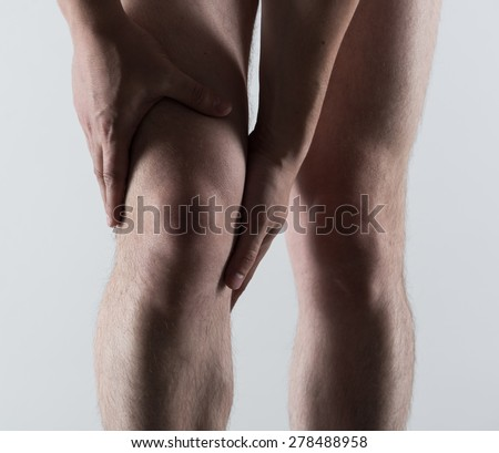 Knee spasm or injury. Young man touching his sore leg.  - stock photo