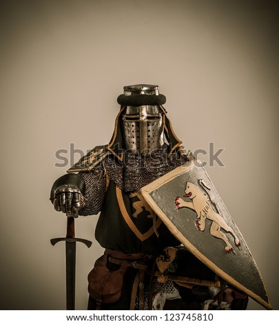 Kneeled medieval knight with sword and shield - stock photo