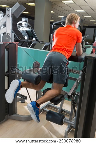 Kneeling leg femoral curl man exercise at gym rear view workout - stock photo