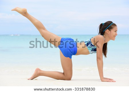 Kneeling leg lift butt toning exercise - Asian fitness woman working out on beach in blue sports bra and shorts strength training her glutes with pilates rear raised legs and donkey kick exercises. - stock photo