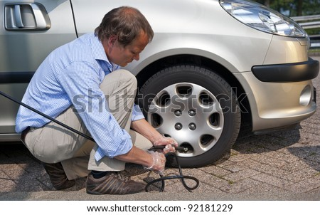 Kneeling man, inflating the right front tyre of his car at a gas station