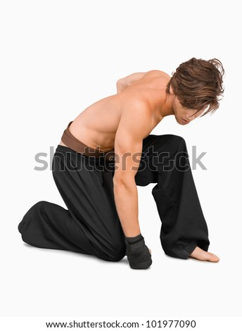 Kneeling martial arts fighter against a white background - stock photo